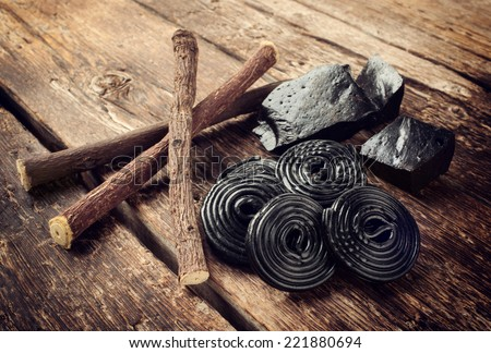 Production steps of licorice, roots, pure blocks and candy on wooden table - stock photo