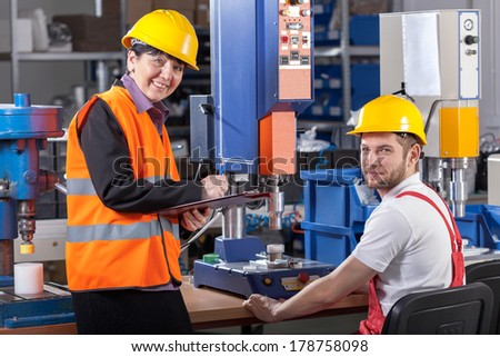 Production worker at workplace and his supervisor - stock photo