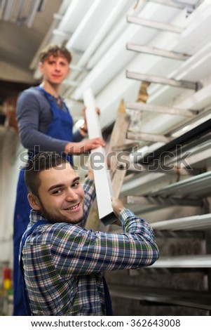 Production workers in uniform with different PVC window profiles indoor - stock photo