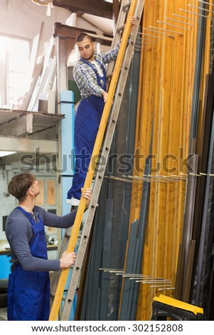 Production workmen in uniform with different PVC window profiles - stock photo