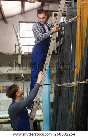 Production young workers in uniform with different PVC window profiles indoor - stock photo