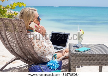 Productive business woman on the beach - stock photo