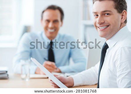 Productive day in office.Happy young businessman in formalwear looking over shoulders while his chief sitting on background  - stock photo
