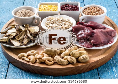 Products containing ferrum (dried mushrooms, bran, buckwheat, livers, dogwood, cashews, oats, lentils, peanuts) on a round cutting board and a blue wooden background  - stock photo