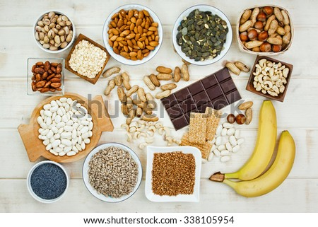Products containing magnesium: pumpkin seeds, poppy seed, cashew nuts, beans, raw cocoa beans, almonds, sunflower seeds, oatmeal, buckwheat, peanuts, hazelnuts, pistachios, dark chocolate, sesame bars - stock photo
