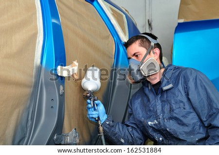 Profesional car painting in a paint booth. - stock photo
