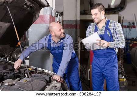 Professinal car mechanic in an automotive repair shop helps insurance agent to calculate loss