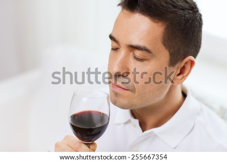 profession, drinks, leisure and people concept - happy man drinking and smelling red wine from glass at home - stock photo