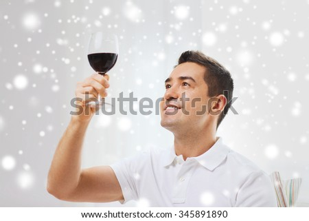 profession, drinks, leisure and people concept - happy man drinking red wine from glass at home over snow effect - stock photo