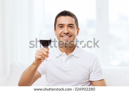 profession, drinks, leisure, holidays and people concept - happy man drinking red wine from glass at home - stock photo