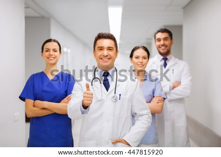 profession, people, health care, gesture and medicine concept - group of happy medics or doctors at hospital corridor showing thumbs up - stock photo