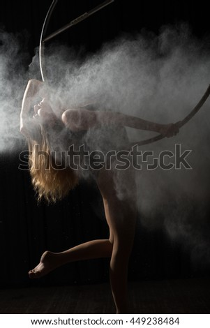 Professional acrobatic woman on aerial hoop with flour - stock photo