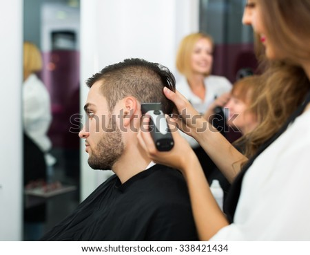 Professional adult woman hairdresser doing hairstyle for young men