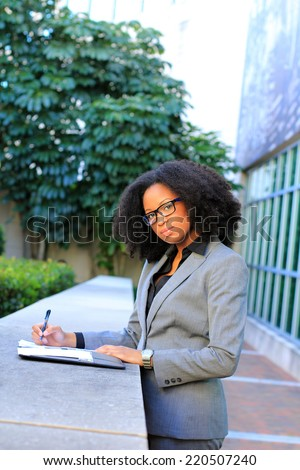 Professional African American Business Woman With Black Hair Outside Natural Pose Writing and Thinking  - stock photo