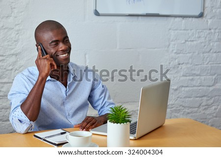 professional african black man talking on mobile cell phone to clients in office with laptop computer - stock photo