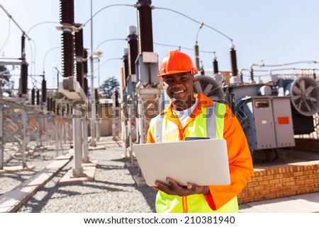professional african electrical engineer using laptop computer in substation