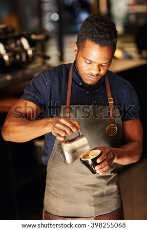 Professional Afro barista pouring frothed milk into a cappucino - stock photo