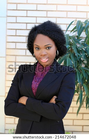 Professional and Attractive African American Business Woman Wearing Black Suit Arms Crossed - stock photo