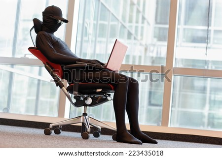 professional anonymous hacker working with laptop in office - stock photo
