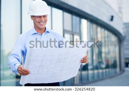 Professional architect is standing and holding blueprint. He is looking at sketch with inspiration and smiling. The man is wearing helmet. Copy space in right side - stock photo