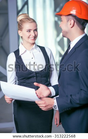 Professional architects are planning new project. They are standing and smiling. The workers are holding a blueprint. The man is wearing an orange helmet - stock photo