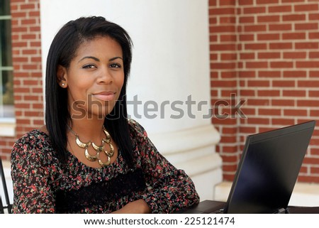 Professional Attractive African American Business Person With Black Hair Serious and Working on Laptop Computer  - stock photo