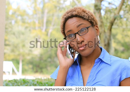 Professional Attractive African American Business Person With Black Hair Wearing Glasses Serious on the Phone  - stock photo