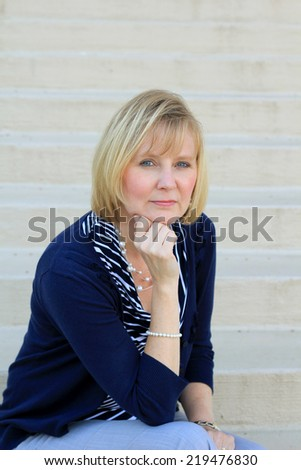 Professional Attractive Blonde Business Woman Hand to Chin Thinking Wearing Blue Shirt  - stock photo