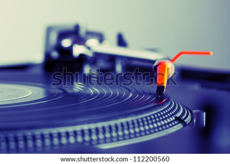 Professional audio equipment for a DJ - turntable playing record with music. Image in hipster tone - violet shadows and red accent on needle - stock photo