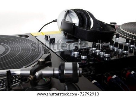 Professional audio equipment for DJ in sound recording studio with isolated white background.Headphones laying on sound mixing controller and turntables vinyl records player