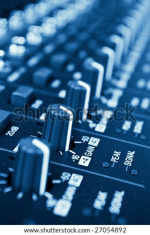 professional audio mixer knobs with shallow depth of field - blue toned - stock photo
