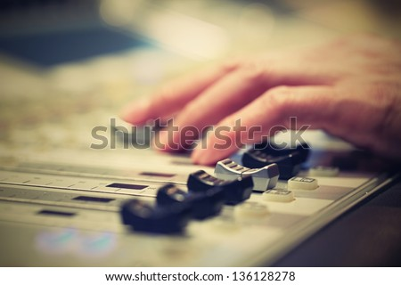 Professional audio mixing console with faders and adjusting knobs - radio / TV broadcasting - stock photo