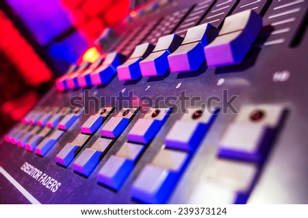 Professional audio sound mixer with buttons and sliders .  Selective focus . A little of DOF.