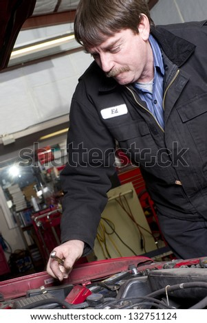 Professional Automotive Technician Works Under the Car Hood in Auto Repair