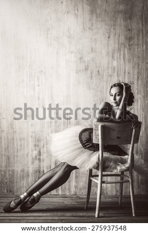 Professional ballet dancer posing at studio over grunge background. Art concept. Toned photo in vintage style. - stock photo