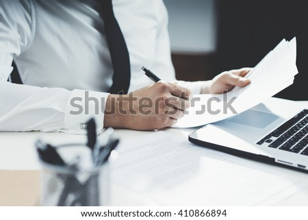 Professional banker working at his office with documents and using modern laptop computer, close-up of male hands signing contract  - stock photo