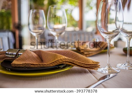 Professional beach restaurant serving, plates and glasses, sea view.
