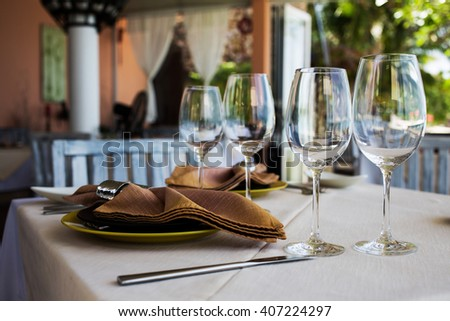 Professional beach restaurant serving, plates and glasses, sea view