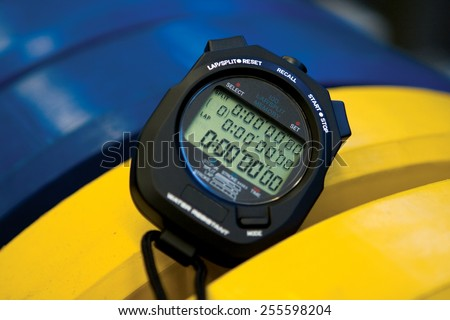 Professional black digital stopwatch and countdown timer with yellow and blue Olympic style rubber bumper plate weights for coaching, sports, personal trainer, interval training and workout routines - stock photo