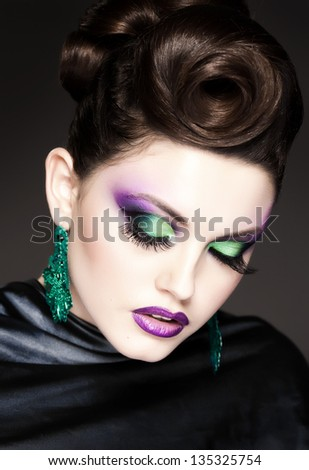 professional blue make-up and hairstyle on beautiful woman face - studio beauty shot - stock photo