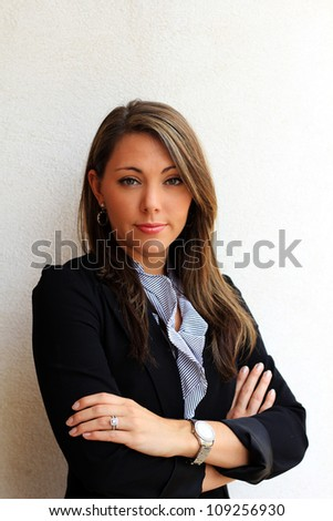 Professional Brunette Business Woman Standing While Serious and Having Arms Crossed - stock photo