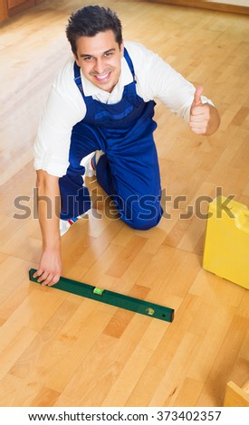 Professional builder checking floor with spirit level indoors