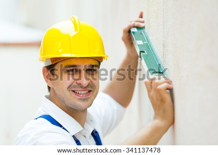 Professional builder posing with spirit level at construction site