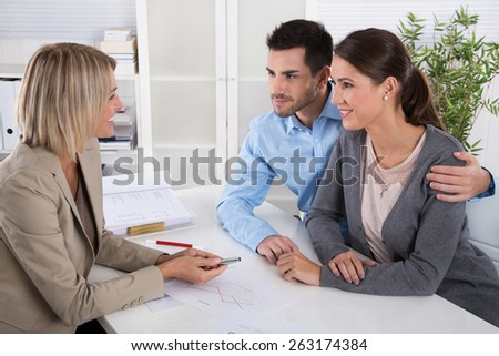 Professional business meeting: young couple as customers and an adviser for finance, investment or insurance. - stock photo