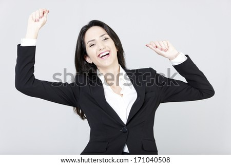 Professional business woman celebrating with her arms raised.