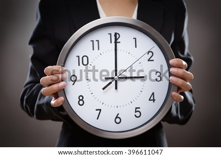 professional business woman holding a large clock