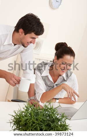 Professional businessman and businesswoman at the office working together