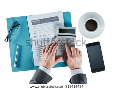 Professional businessman at desk checking a financial report and using a calculator