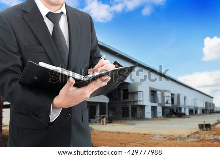 Professional businessman booking with blurred construction factory or warehouse building site background, industrial business concept - stock photo