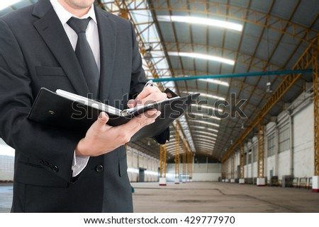 Professional businessman evaluation factory with blurred construction factory building site background, industrial business concept - stock photo
